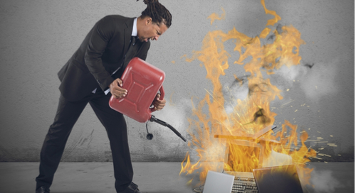 Frustrated man trying to solve computer problem by burning computers