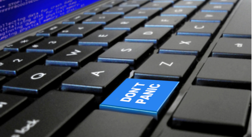 "Computer keyboard with ""Don't Panic"" key highlighted in blue"