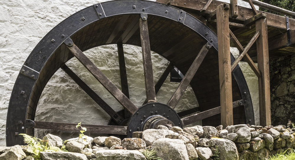 Iron and wood cornmill wheel lined with rocks