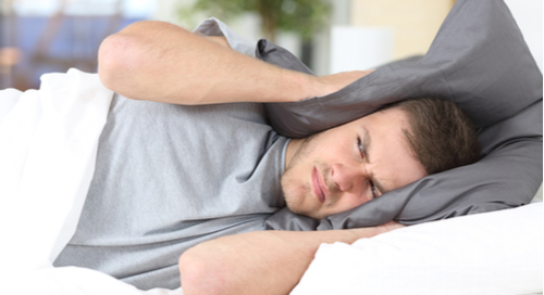 Man trying to block out noise with pillow around his head