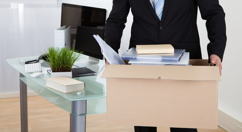 Businessman leaving with personal items in box