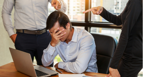 Businesspeople blaming frustrated colleague