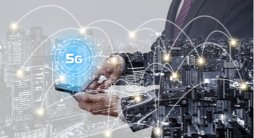 person holding a smartphone with 5G written above it