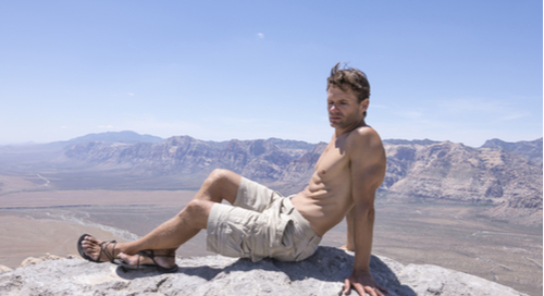 Muscular man in cargo shorts on mountain top