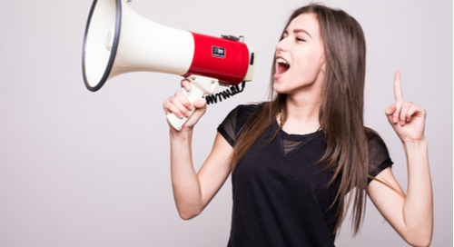 Girl with finger pointed up yelling into a megaphone