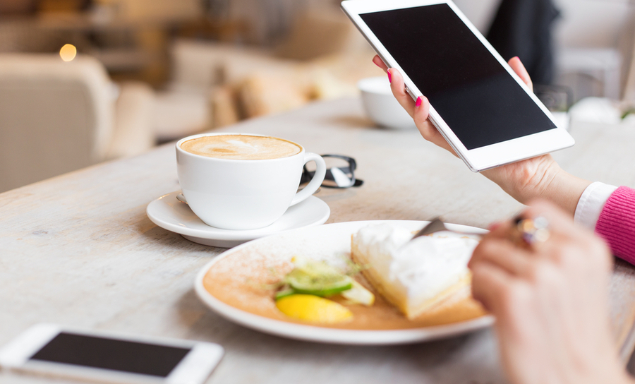 Woman holding tablet and preparing to eat breakfast