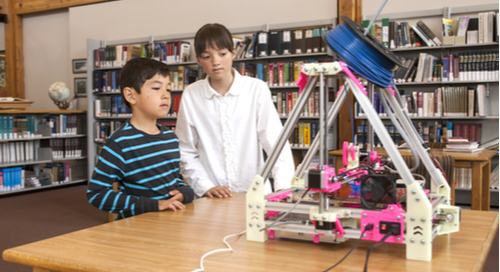 Two children watching a 3D printer at a