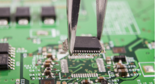 An IC being placed on a green PCB with tweezers
