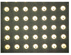 Top view of multiple vias that have been laser-drilled off-center.