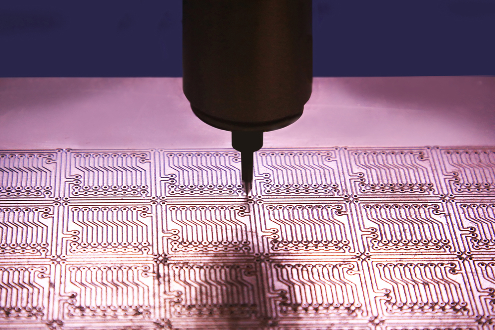 Drilling holes in the printed circuit board for mounting chips.